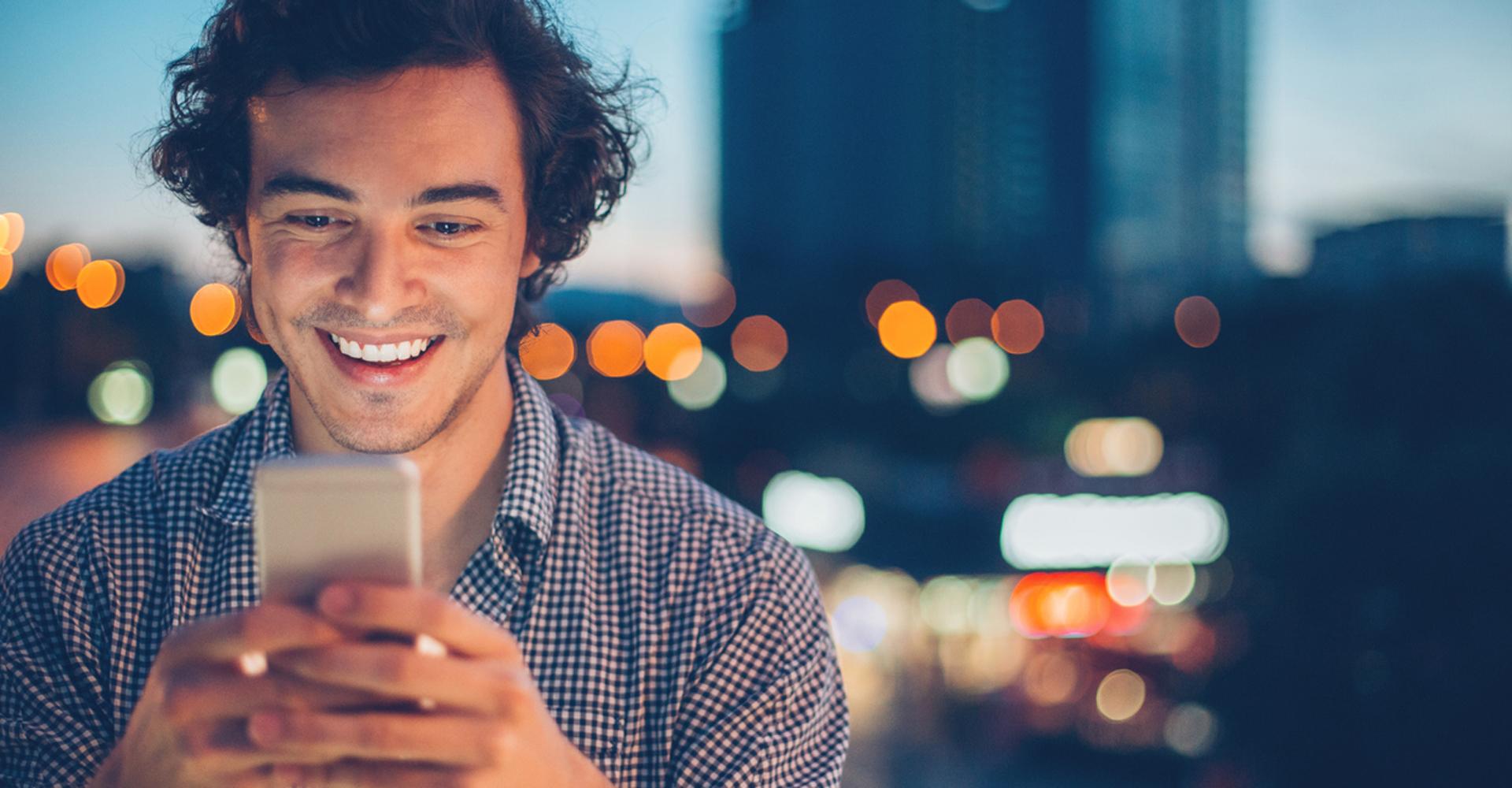 Ein Mann schaut lachend auf sein Smartphone, im Hintergrund sieht man eine City-Skyline.