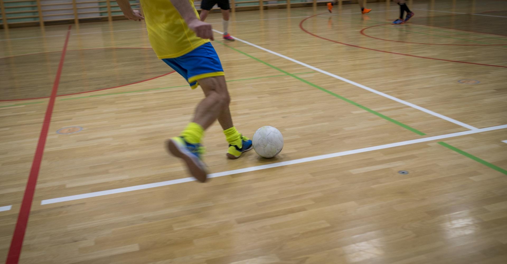 Junger Sportler spielt Fußball in der Halle
