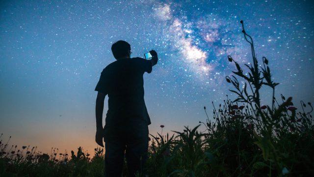 Junger Mann macht via Smartphone Fotos mit Langzeitbelichtung.