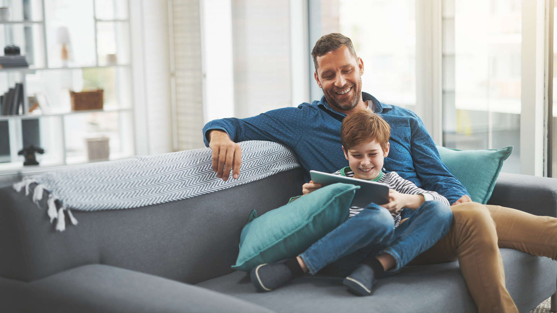 Ein Vater spielt mit seinem Sohn am Tablet.