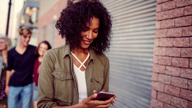 Frau liest sich am Smartphone Tipps für Threema durch.