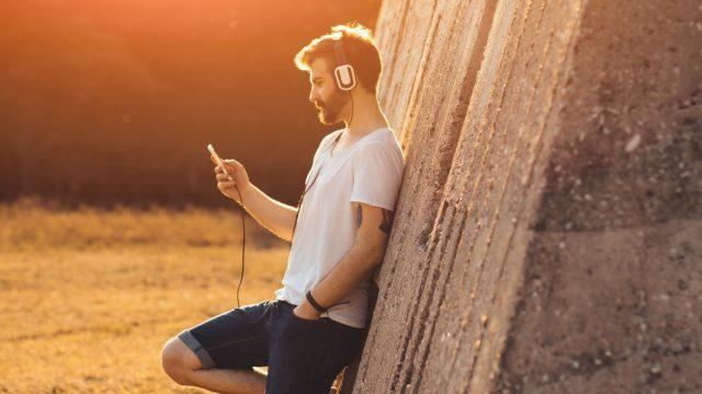 Junger Mann lehnt an einer Mauer und hört seine Lieblingsmusik.