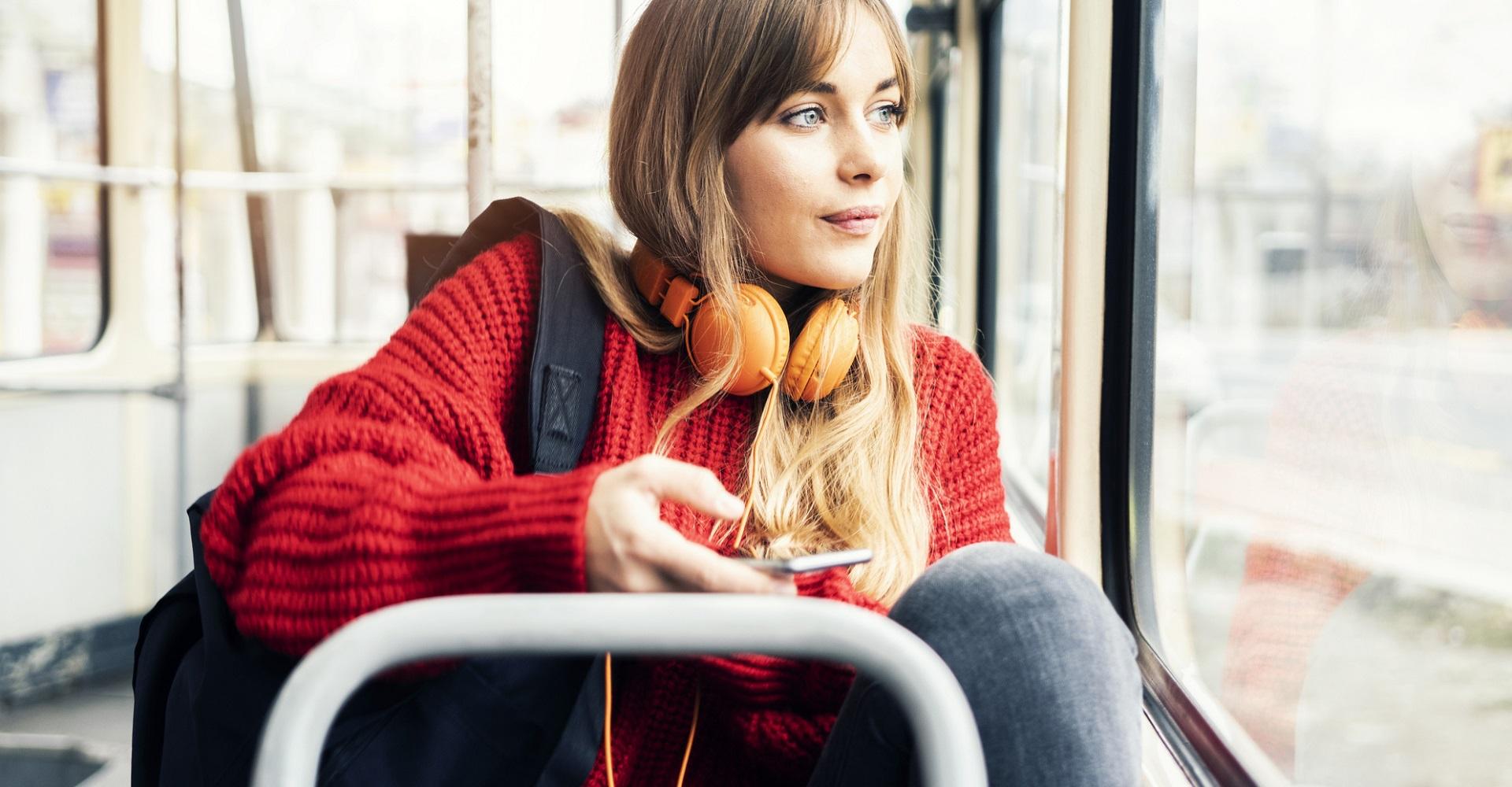Junge Frau sitzt im Bus und hört ihre Lieblingsmusik.