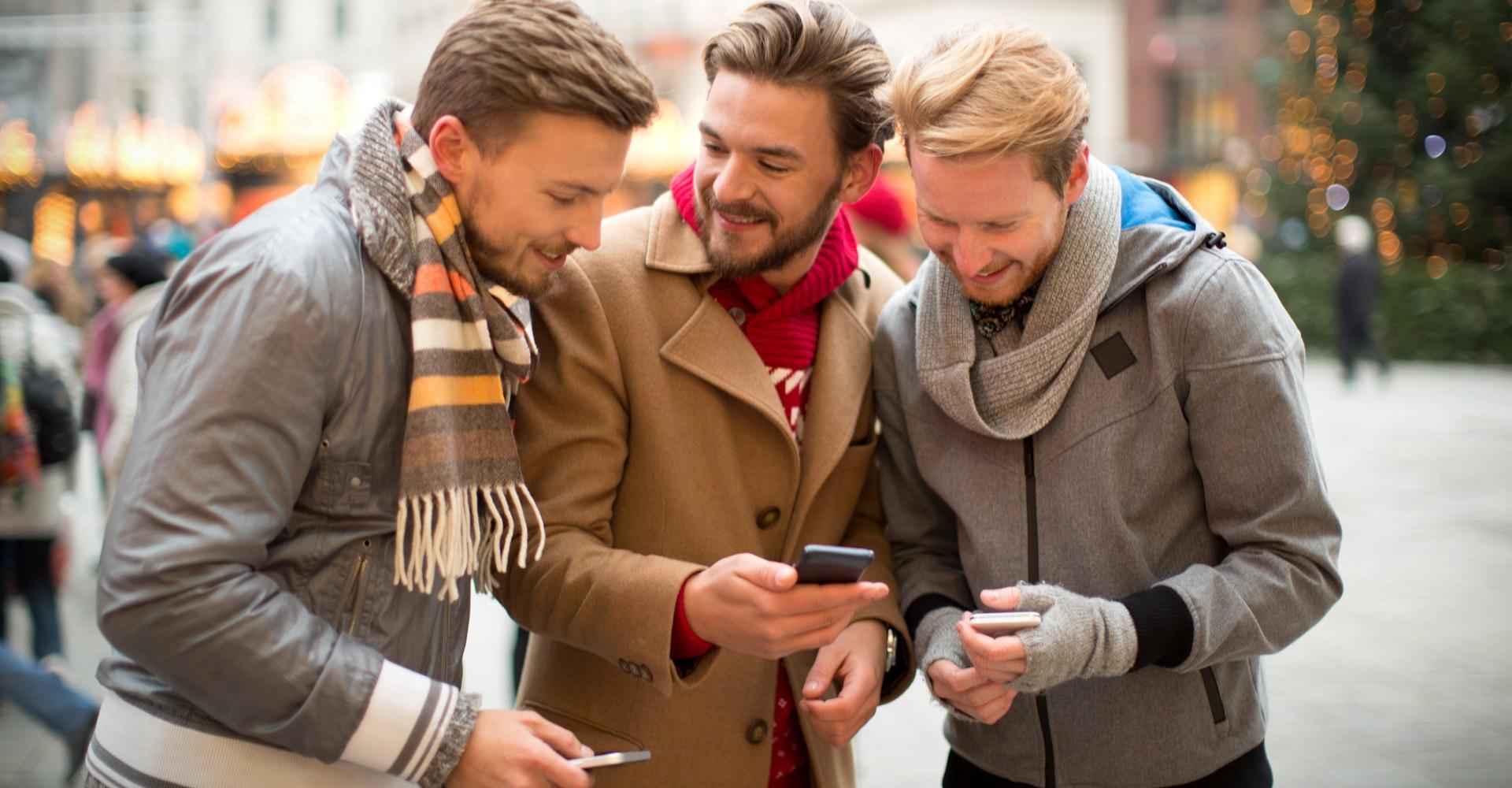Eine Gruppe junger Männer spielt Skat via Smartphone.