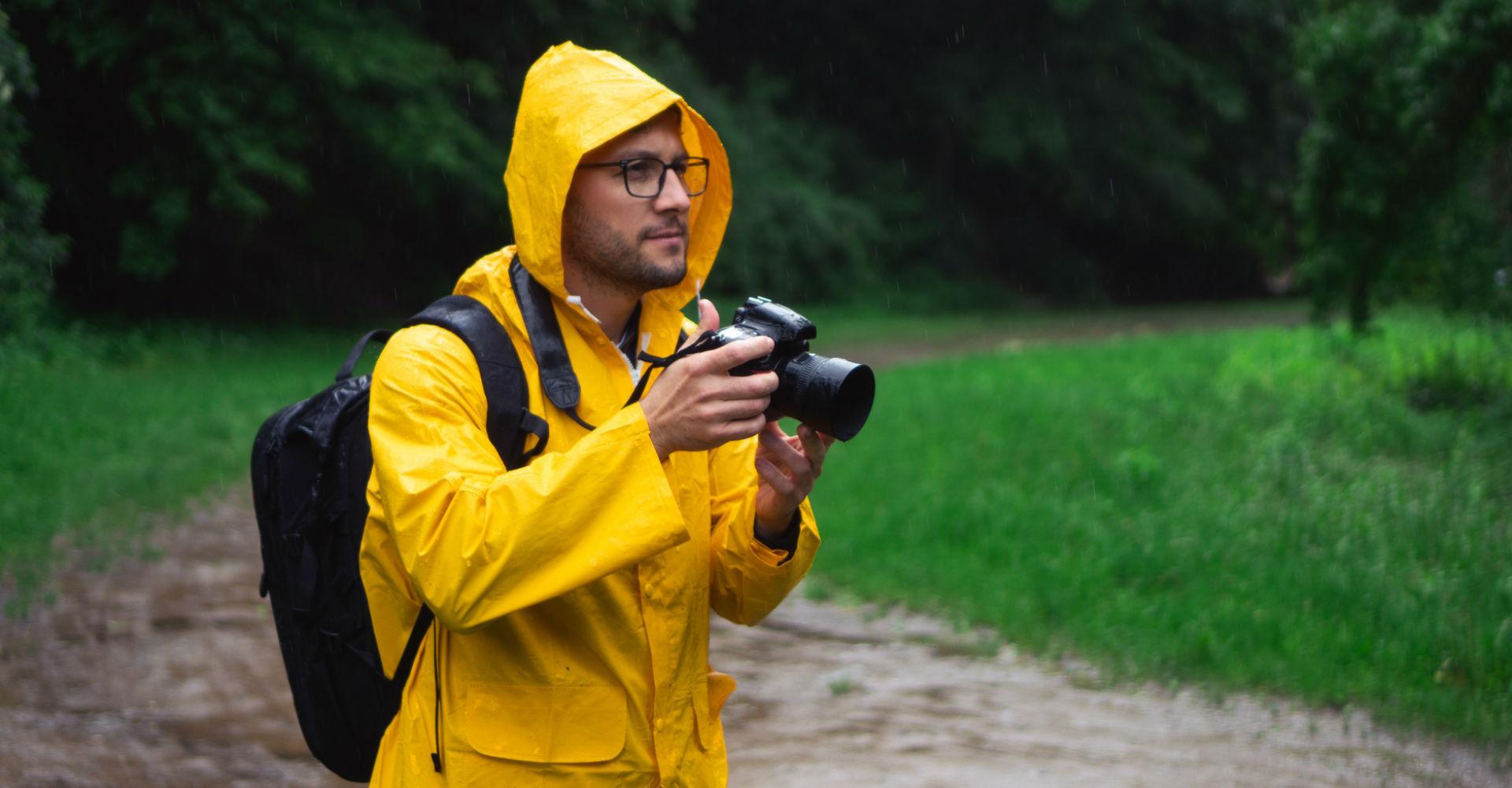 Mann fotografiert mit seiner Kamera im Regen.