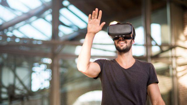 Ein Mann trägt in einem offenem Raum mit Virtual Reality-Brille