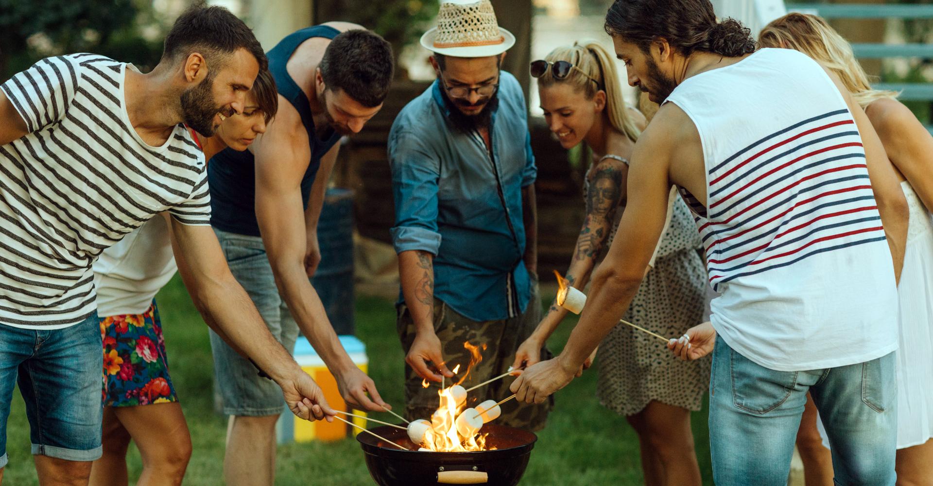 Junge Leute stehen mit Marshmallows am Grill