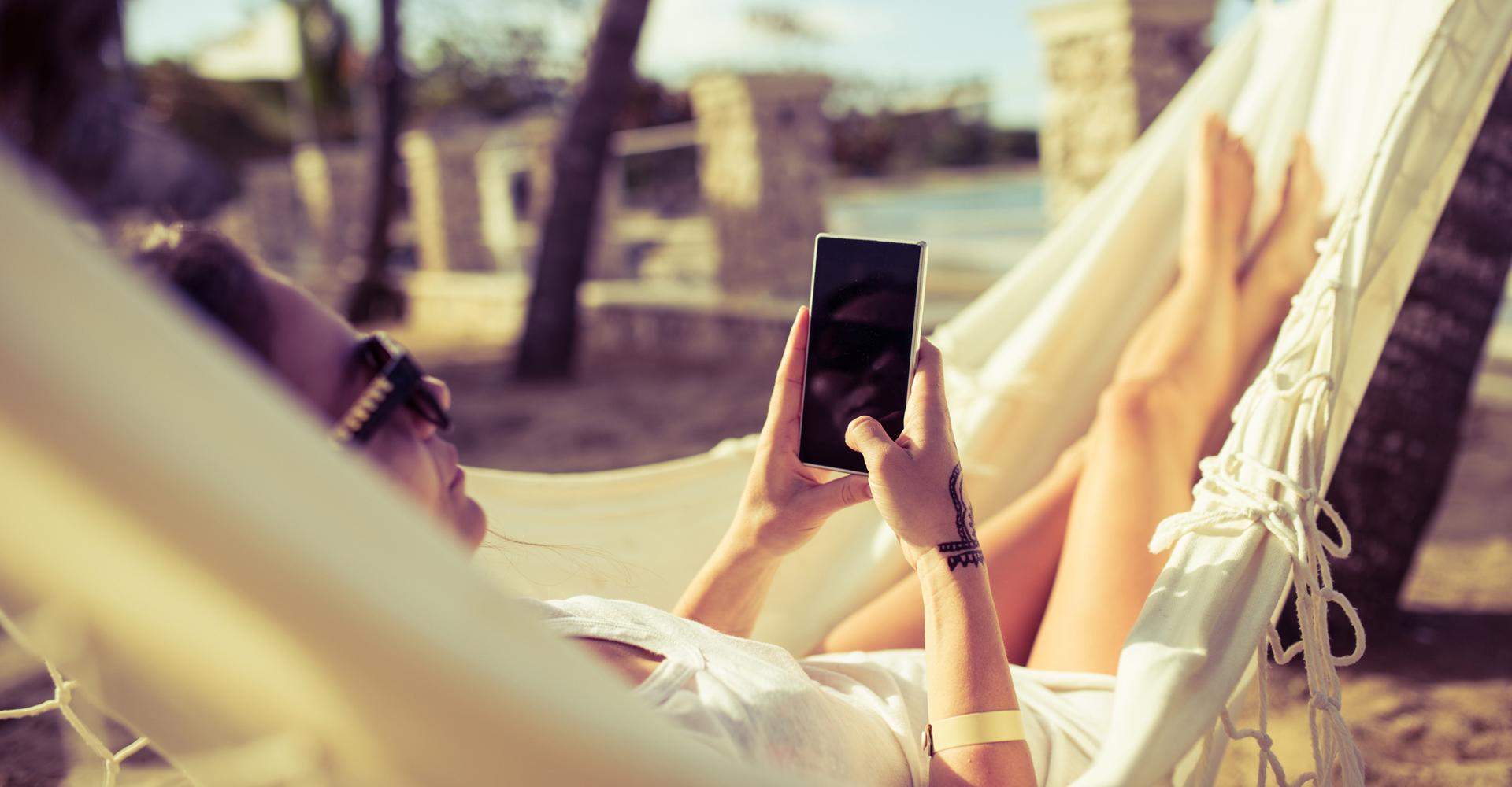 Frau entspannt in ihrer Hängematte am Strand und nutzt Lese-Apps