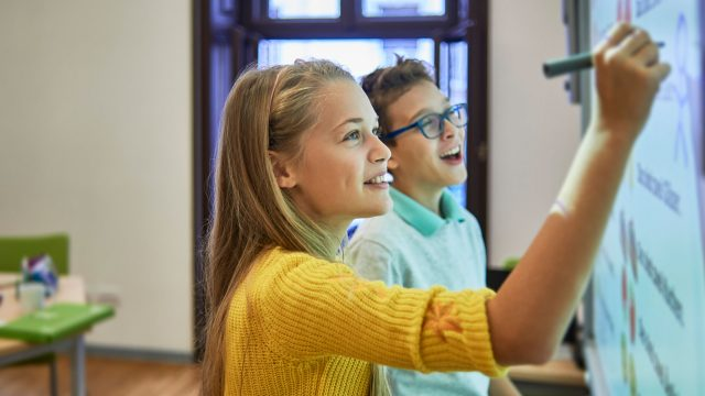 Zwei Schüler schreiben auf ein Smartboard - Bildung in der Digitalisierung zum Tag der Jugend