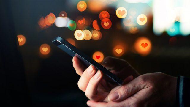 Handy in Händen und Herz-Icons