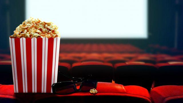 Popcorn steht im Kino vor der Leinwand.