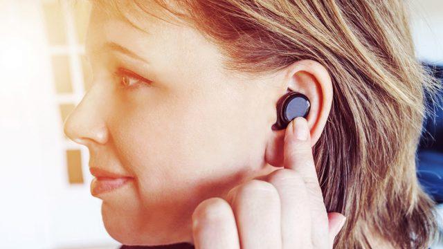 Junge Frau hört Musik über ihre Bluetooth-Kopfhörer.