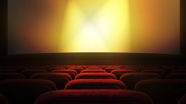 Im Kino sitzen und auf die Leinwand schauen.