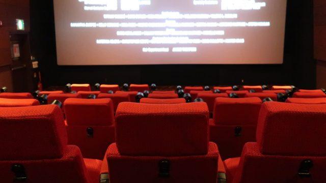 Rote Kinositze vor einer hellen Filmleinwand.