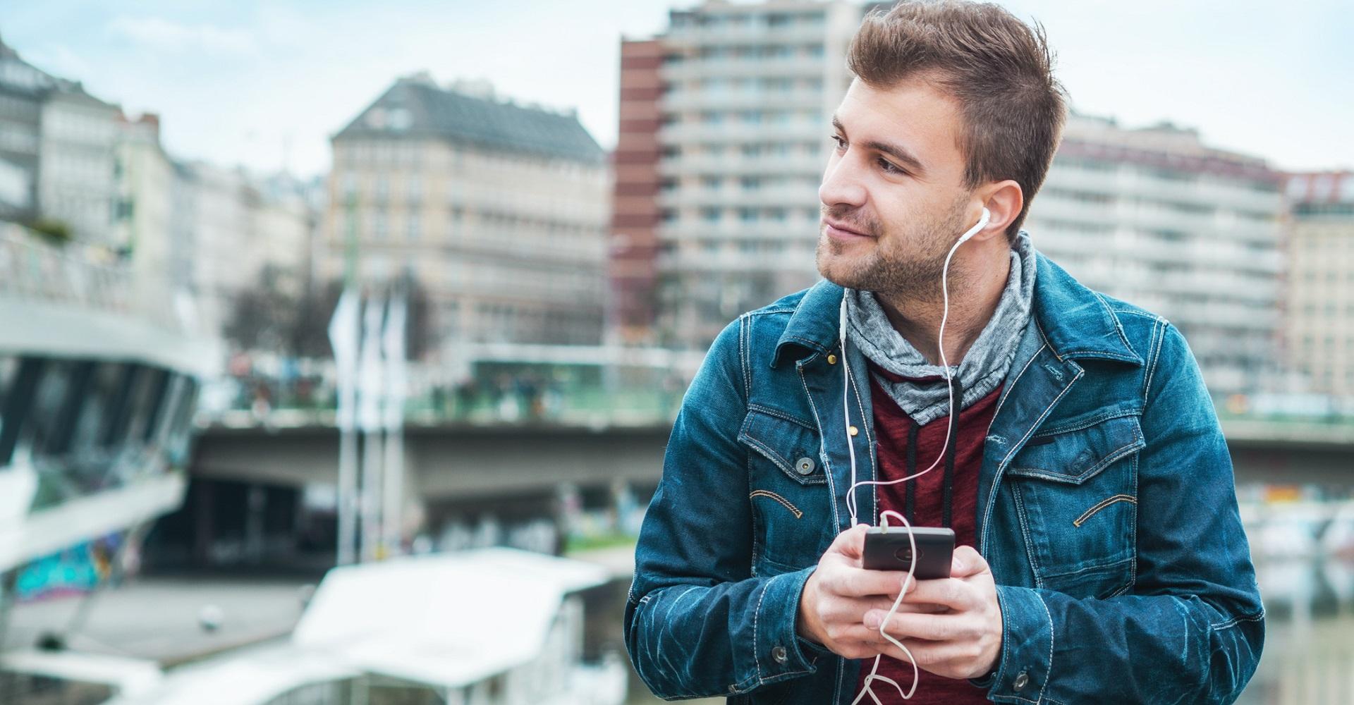 Junger Mann hört Musik über Spotify