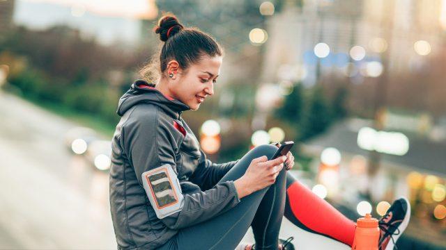 Frau mit Sportklamotten und Handy