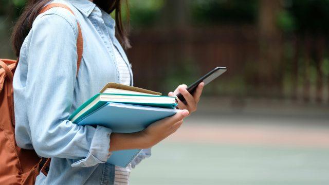 Schülerin mit Smartphone und Büchern
