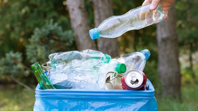 Hand wirft Plastikflaschen am World Clean Up Day 2019 in Mülleimer