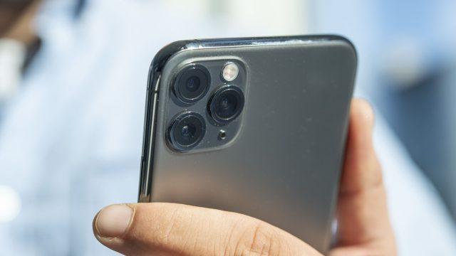 Mann drückt eine Taste am iPhone 11, um das Gerät auszuschalten.