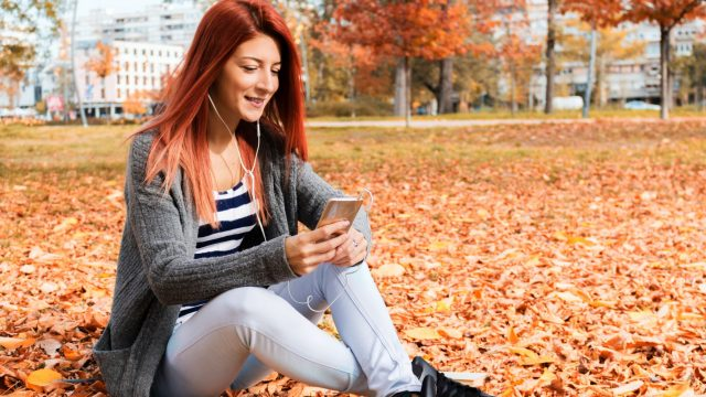 Junge Frau chattet am Smartphone via Threads.