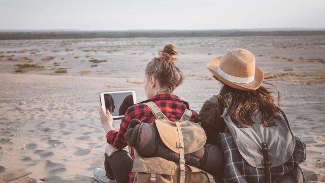 Zwei Mädchen mit Tablet am Strand