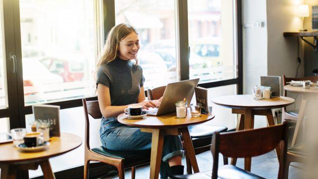 Junge Frau mit Laptop im Cafe