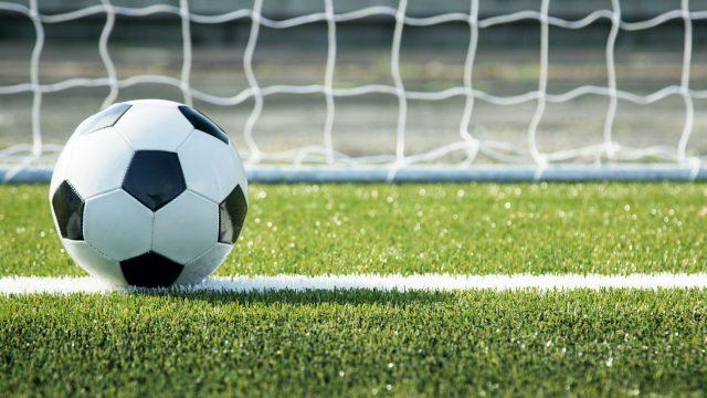 Ein Fußball rollt ins Tor.