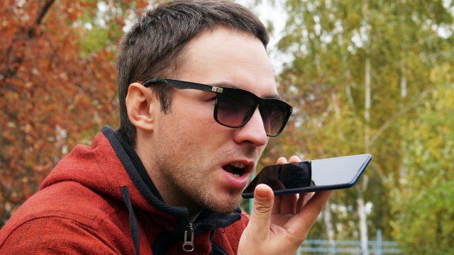 Junger Mann spricht am iPhone mit Siri, um Musik abzuspielen.