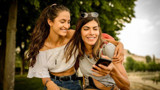 Zwei Frauen schauen auf ein Handy