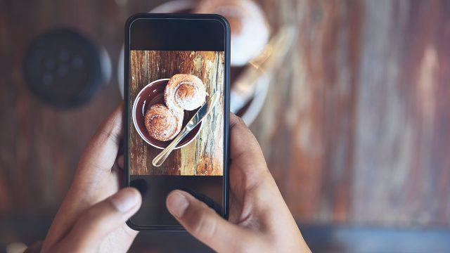 Eine Frau fotografiert ihr Essen