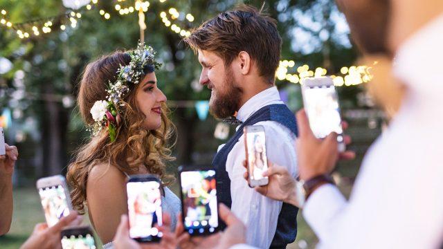 Gäste fotografieren ein Brautpaar