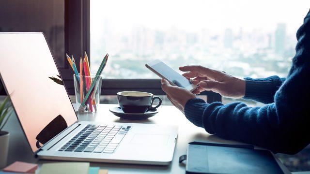 Person mit Handy in der Hand sitzt vor einem Laptop