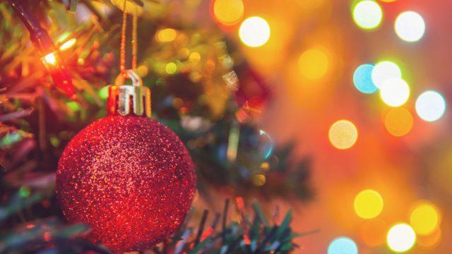 Rote Kugel hängt im Weihnachtsbaum.