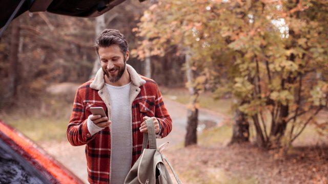 Junger Mann lädt Android 10 auf sein Samsung-Smartphone.