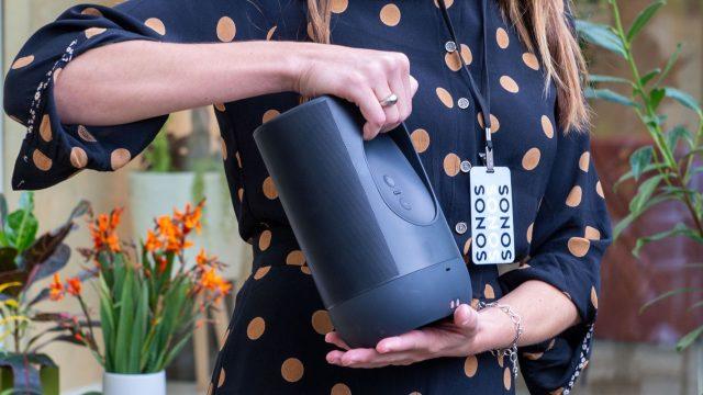 Frau hält den mit Spotify verknüpften Sonos-Lautsprecher in der Hand.