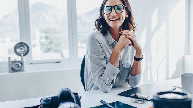 Eine Frau sitzt an einem Bürotisch und lacht