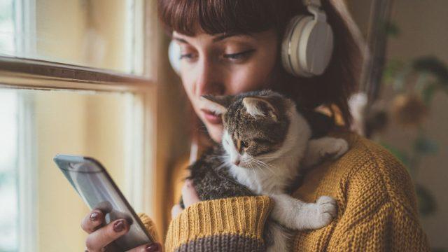 Frau hält Katze im Arm und hört mit ihrem Android-11-Handy Musik.