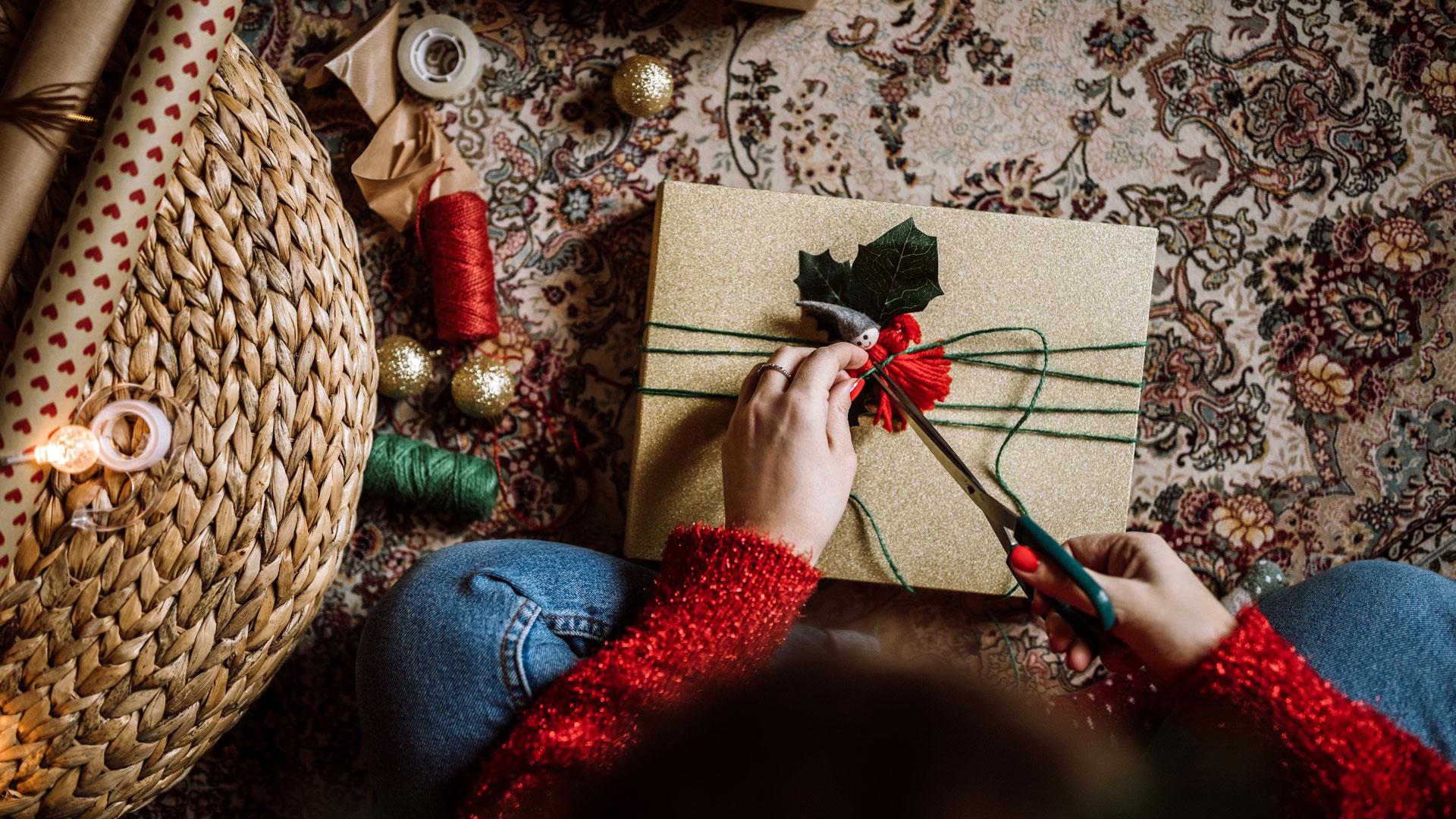Eine Frau mit rotem Pulli packt ein Weihnachtsgeschenk ein und verziert es, neben ihr liegt Garn und Geschenkpapier..