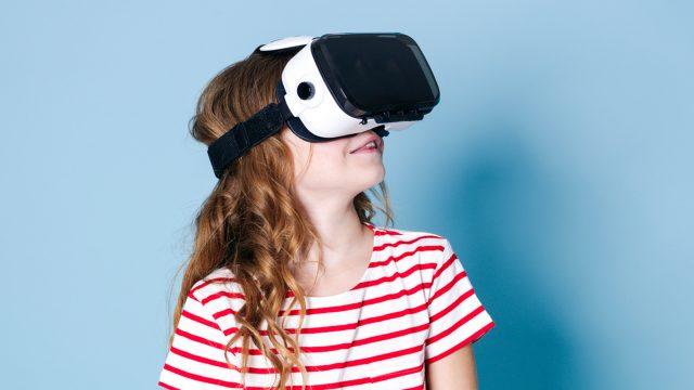 Junges Mädchen schaut sich mit einer VR-Brille digitale Mutmacher an