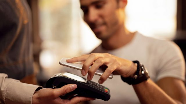 Mann zahlt kontaktlos via Google Pay auf dem Smartphone.