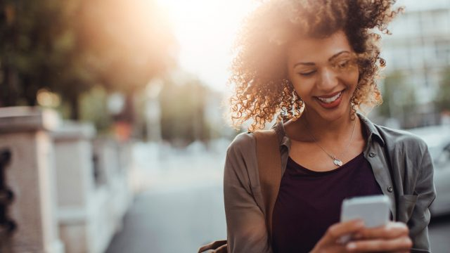 Frau mit lockigen Haaren und Smartphone in der Hand nutzt Highspeed-Internet ohne Limit dank DataPush von Vodafone