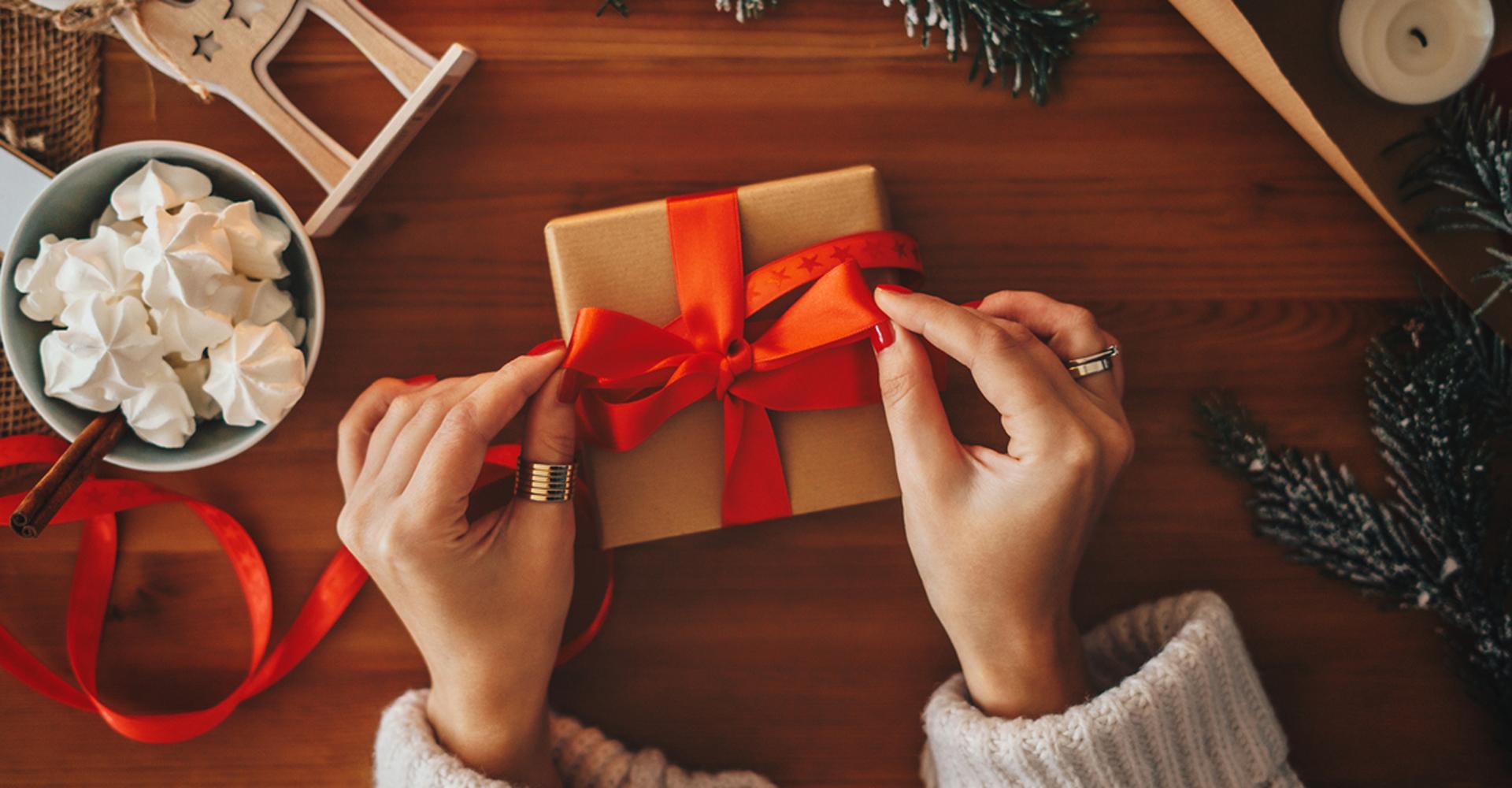 Frau verpackt Geschenk, in dem smarter Schmuck ist.