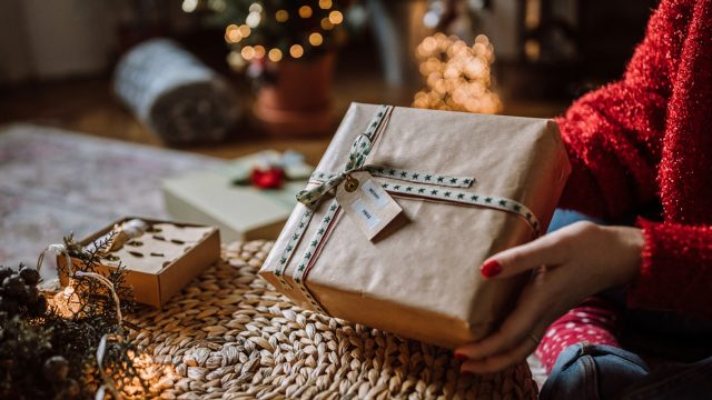 Frau verschenkt Päckchen, in dem smarter Schmuck eingepackt ist.