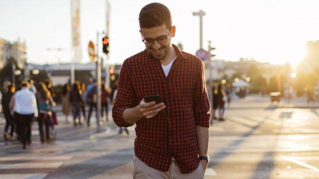 Mann schaltet am Android-11-Smartphone den Dark Mode ein.