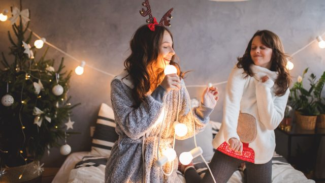 Junge Frauen singen zu Weihnachts-Playlists von Spotify.