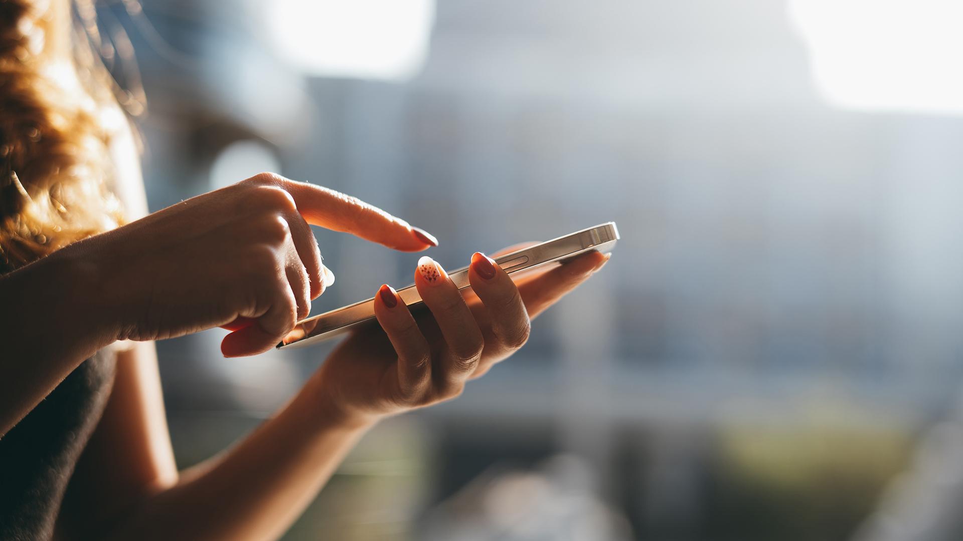 Zu sehen ist der Oberkörper einer Frau, die etwas auf ihrem Smartphone auswählt.