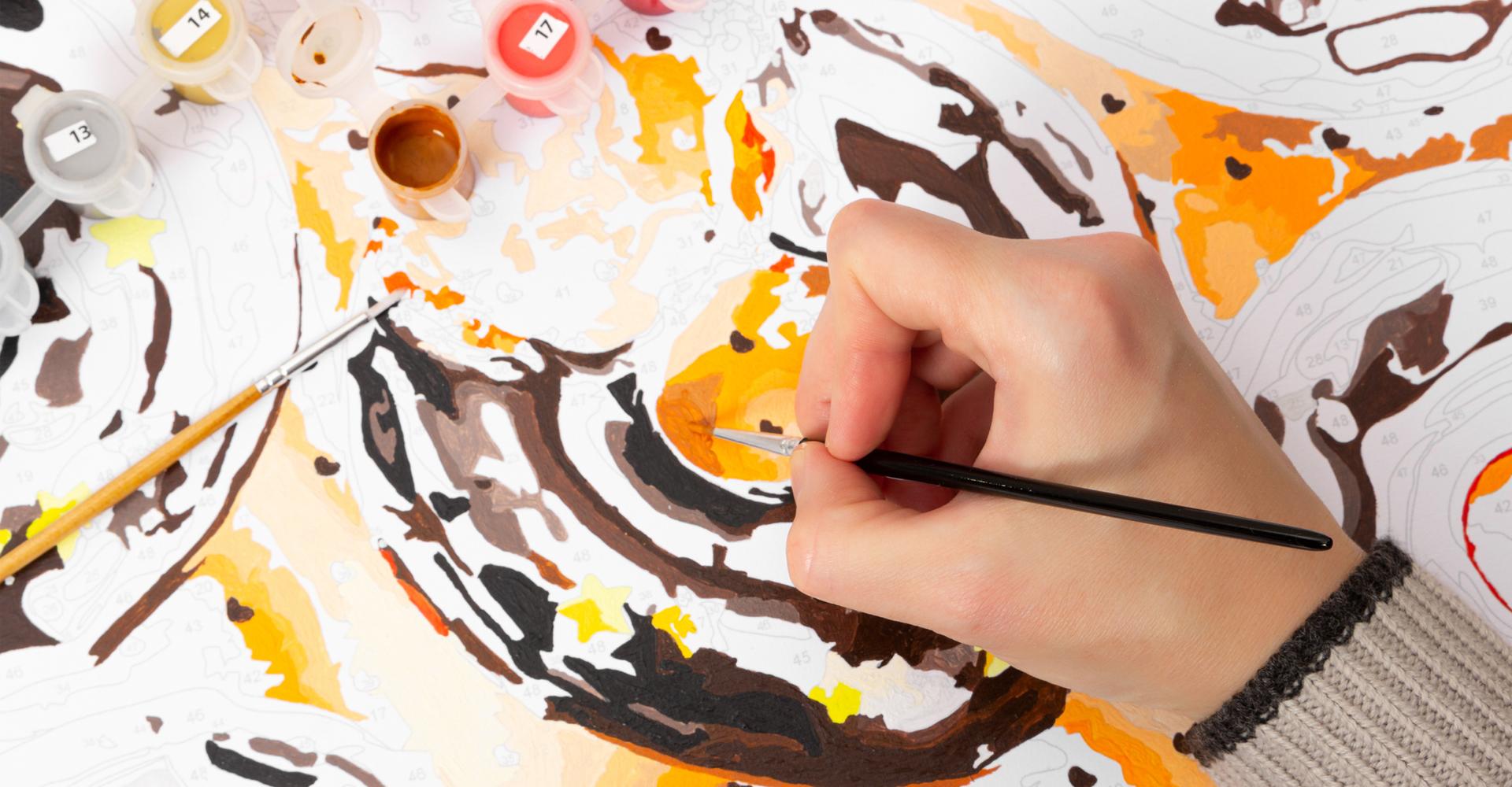 Hand mit Pinsel und Malen-nach-Zahlen-Bild