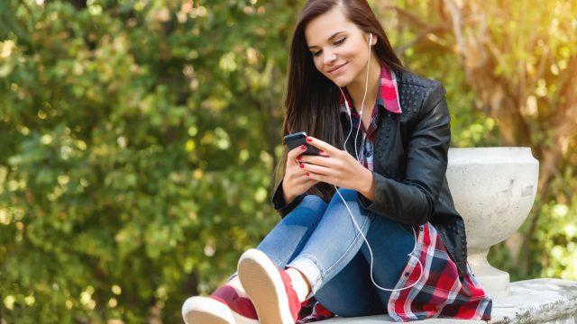 junge Frau betrachtet Smartphone