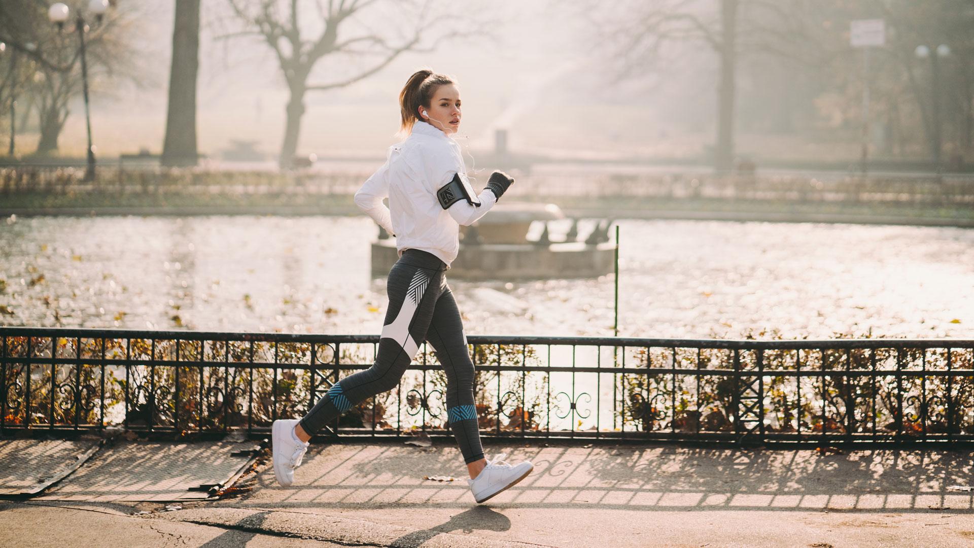 Eine joggende Frau, die sich mit Fitness-Tracker und Sport-Apps fit hält