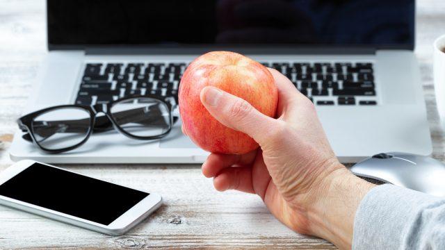 Macbook mit Hand und Apfel